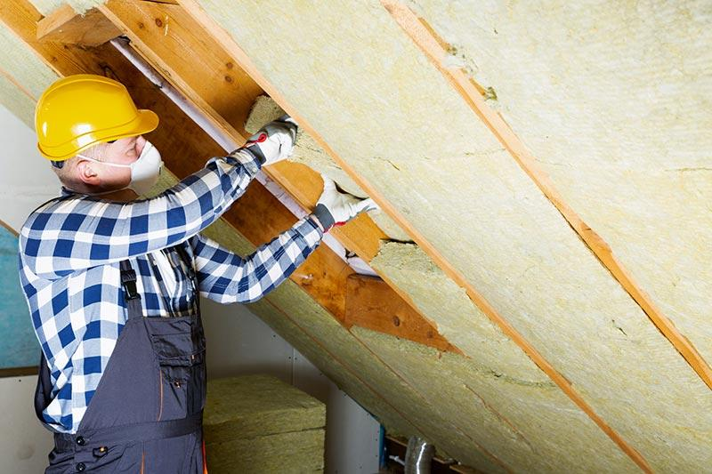 Man installing insulation in an attic. Installing attic insulation can increase home value.