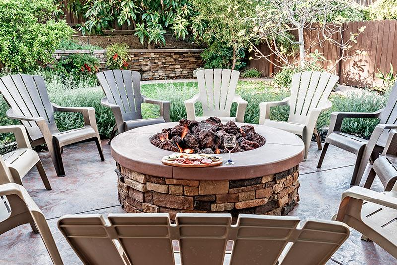 Photo of a stone fireplace on a small patio. An example of backyard landscaping to increase home value.