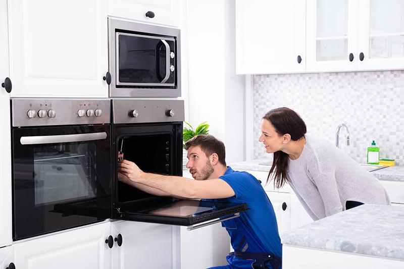 Man repairing a kitchen appliance as a woman watches. Repair and replace appliances and fixtures to boost home value.