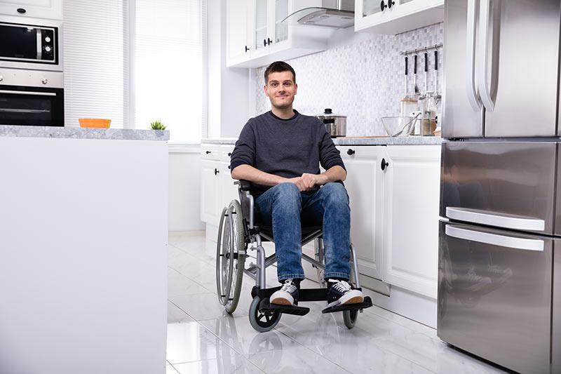 Smiling man on wheelchair in an accessible kitchen. Using universal home design in renovations can increase home value.